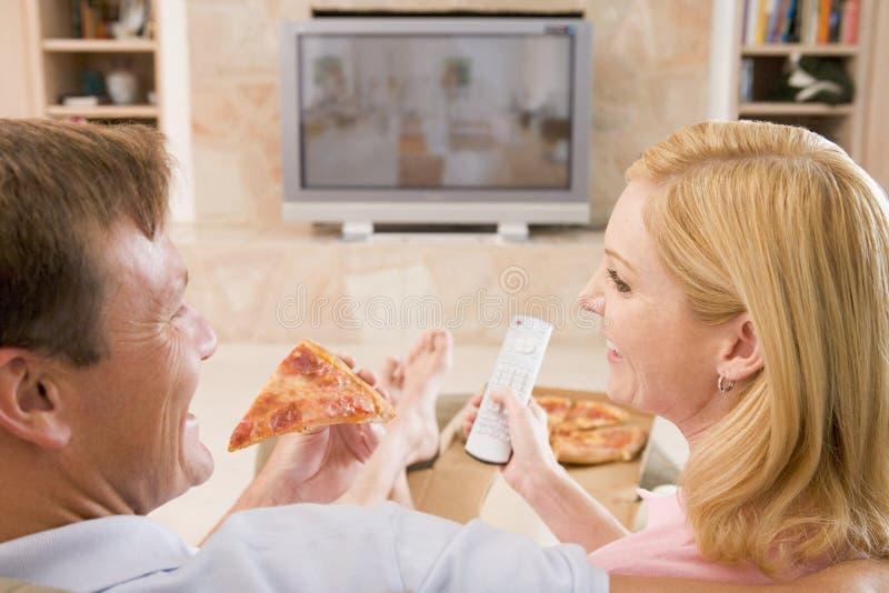 par som tycker om den främre pizzatv:n royaltyfria bilder