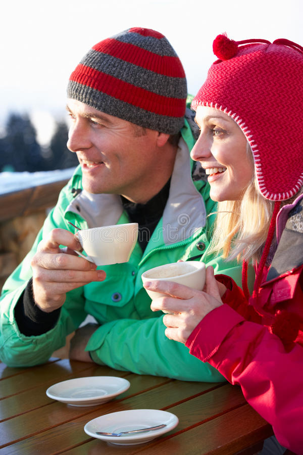 Par som tycker om den varma drinken i Cafe på, skidar semesterorten arkivfoton