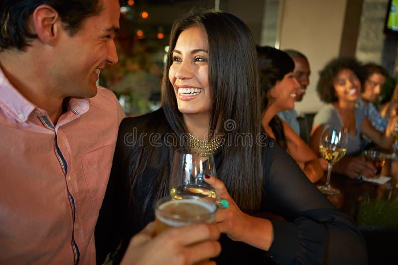 Par som tycker om drinken på stången med vänner royaltyfri bild