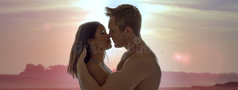 Par som tycker om en romantisk solnedgångkyss royaltyfri fotografi
