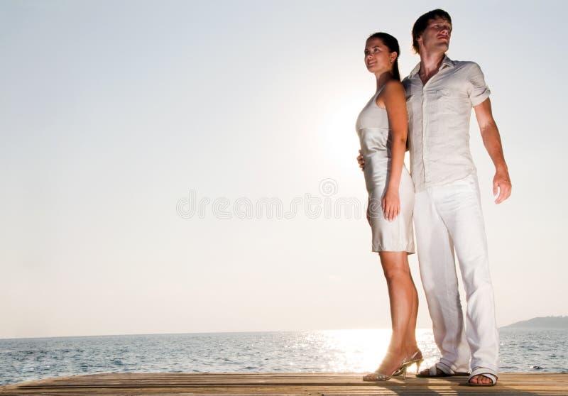 par som tycker om krama sommarsolnedgång arkivbild