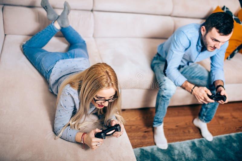 Par som tycker om lekar på allmänt dobbelkonsolsammanträde på soffan i fri tid Detaljer av den moderna livsstilen royaltyfria bilder