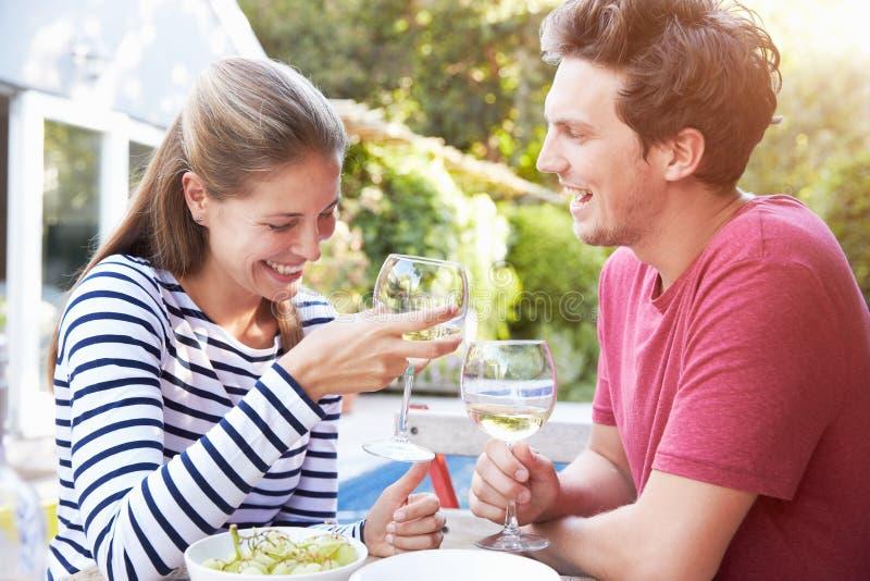 Par som tycker om utomhus- drinkar i trädgård arkivbilder