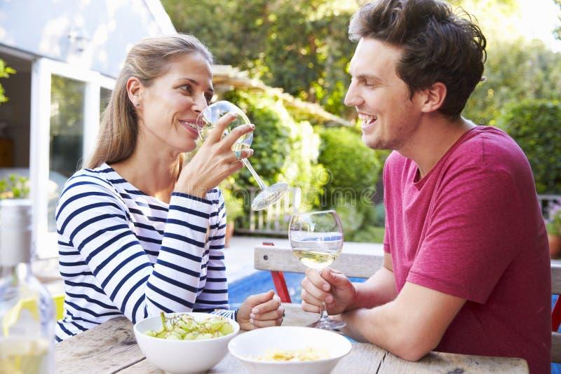 Par som tycker om utomhus- drinkar i trädgård arkivbild