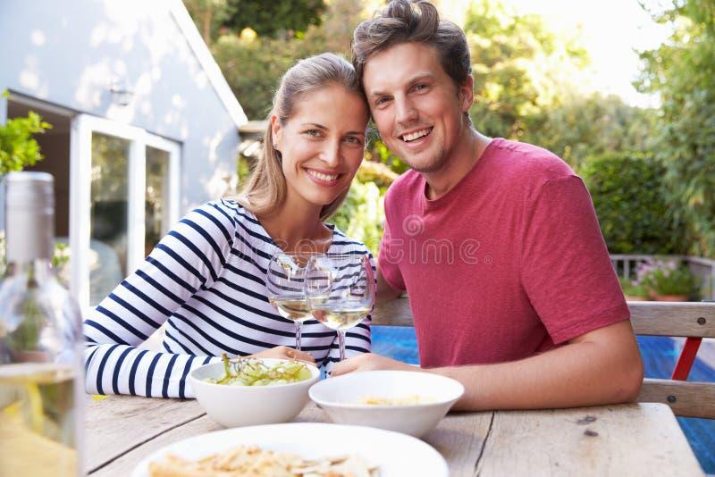 Par som tycker om utomhus- drinkar i trädgård arkivfoton