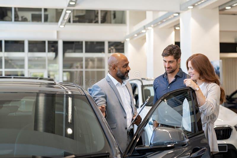 Par som undersöker den nya automatiskn med bilåterförsäljaren royaltyfri foto