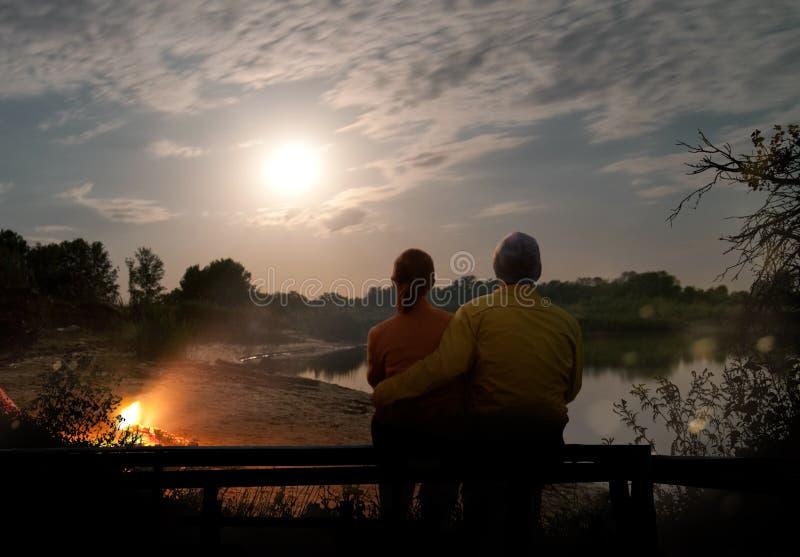 Par som utomhus campar med lägereld och tältet arkivbilder