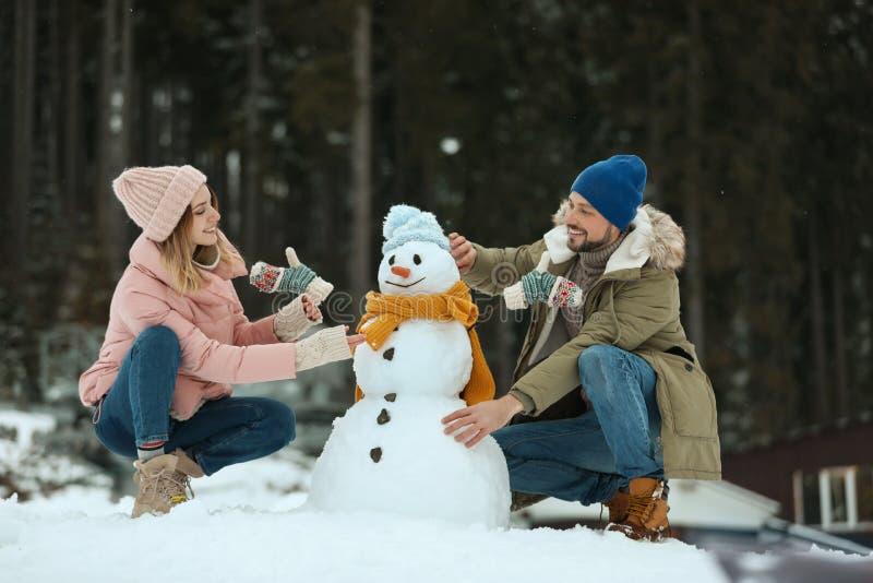 Par som utomhus gör snögubben Vinter royaltyfri fotografi