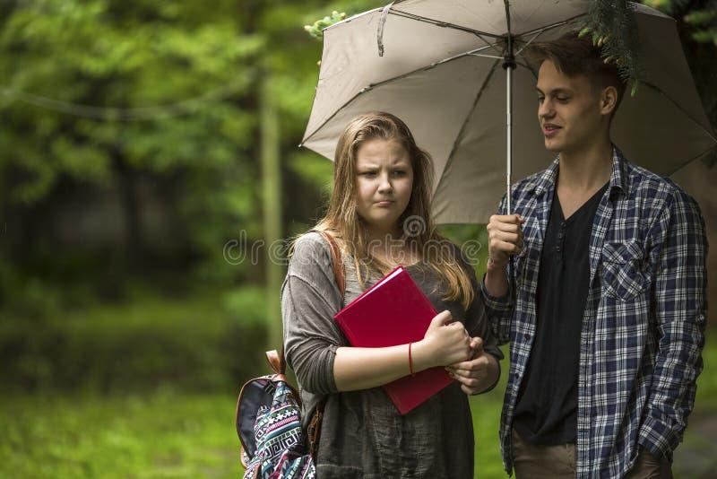 Par som utomhus talar Flicka med en röd bok i hans händer och grabben med paraplyet royaltyfri foto
