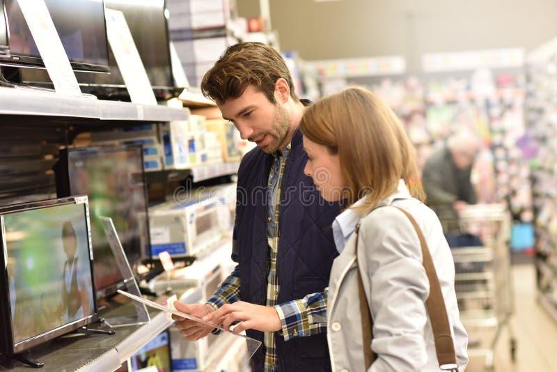Par som väljer en tvuppsättning i supermarket arkivfoto
