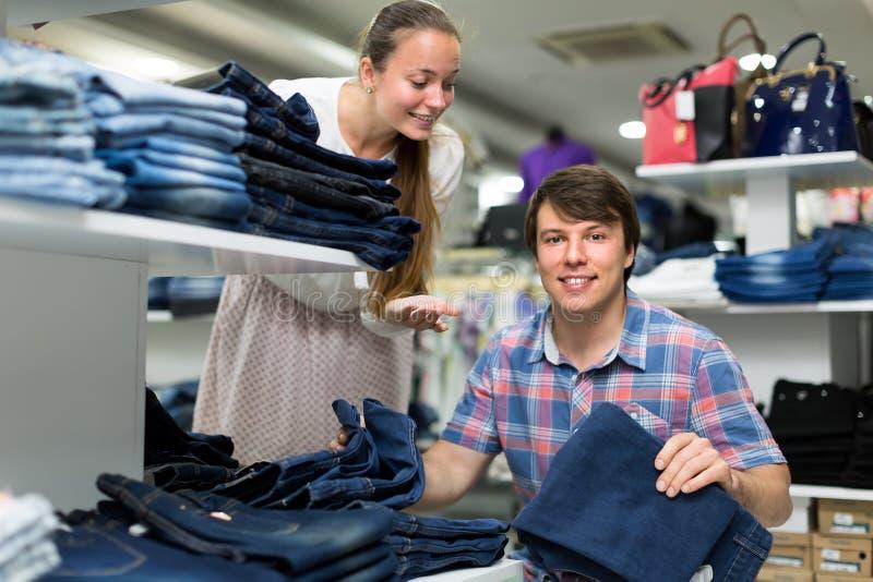 Par som väljer jeans, near hyllan royaltyfria bilder