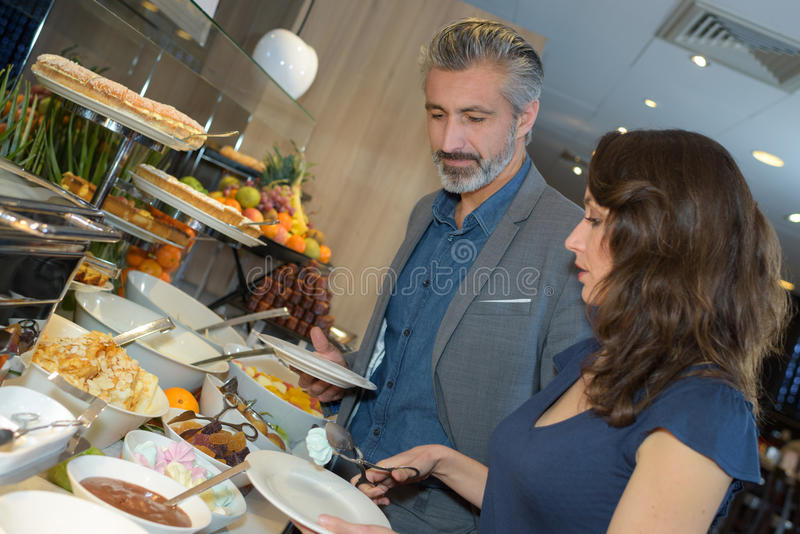 Par som väljer mat i bufférestaurang royaltyfria foton