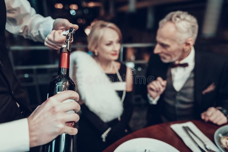 Par som vilar i öppet vin för restaurang och för uppassare royaltyfri bild