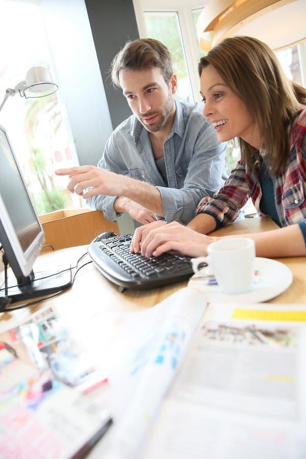 Par som websurfing i cybercafe royaltyfri bild
