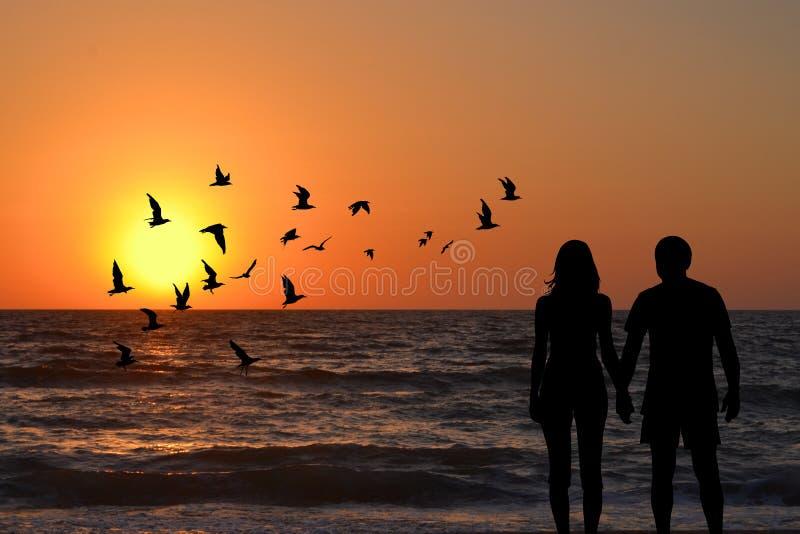 Par sylwetki trzyma ręki patrzeje wschód słońca na plaży fotografia royalty free