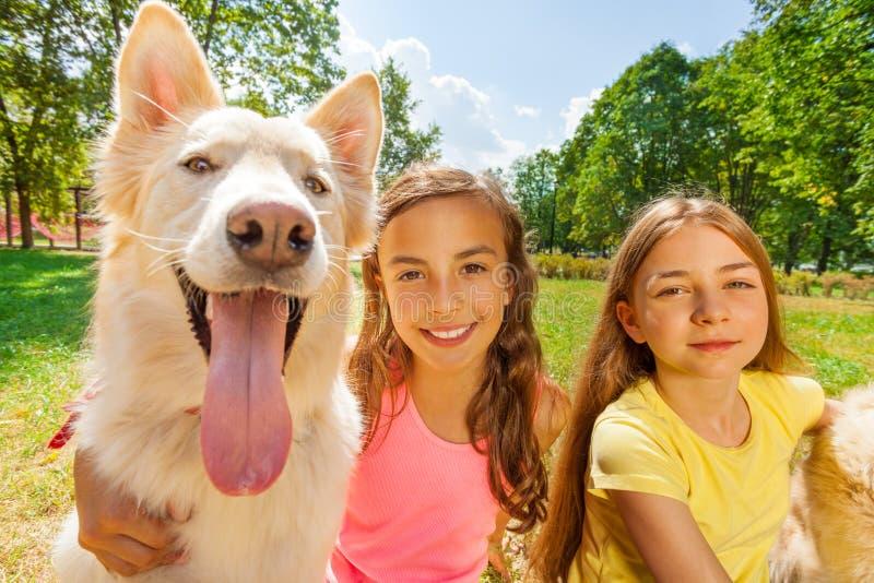 Par szczęśliwe dziewczyny z śmiesznym psem obraz stock