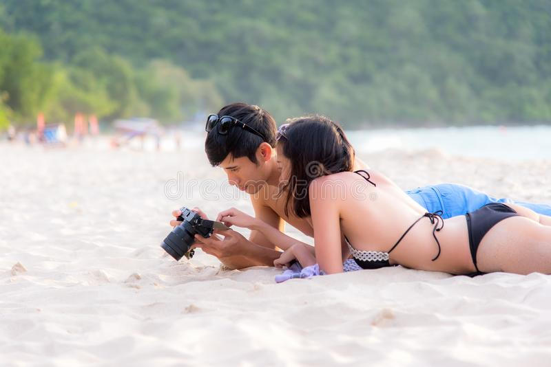 Par tycker om och lycklig gyckel på stranden som skrattar se tillsammans bilder för foto för lopp för sommarsemester på retro tap arkivbild