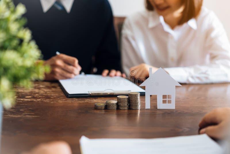 Par undertecknade ett avtal f?r att k?pa ett hus fr?n m?klaren Mynt som staplar pengar- och modellhus som f?rl?ggas p? tabellen royaltyfri bild
