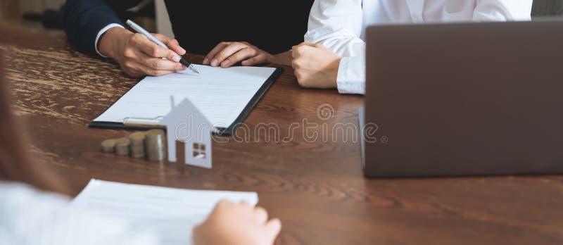 Par undertecknade ett avtal f?r att k?pa ett hus fr?n m?klaren Mynt som staplar pengar- och modellhuset som förläggas på tabellen fotografering för bildbyråer
