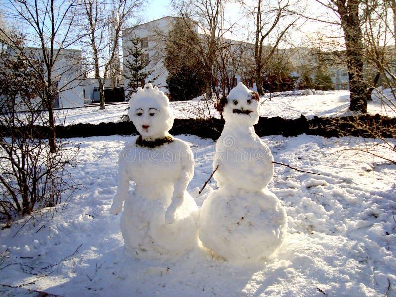 Para śmieszni dekorujący bałwany, mężczyzna i kobieta w śnieżystym parku, obraz royalty free