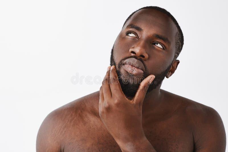 Para afeitar o no, ése es pregunta Afroamericano masculino apuesto pensativo con la barba, colocándose desnuda encima imagenes de archivo