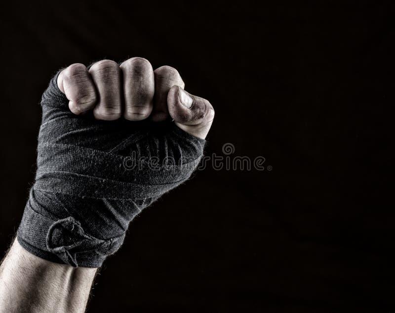 Para arriba levantado puño del atleta envuelto en vendaje negro de la materia textil fotografía de archivo libre de regalías