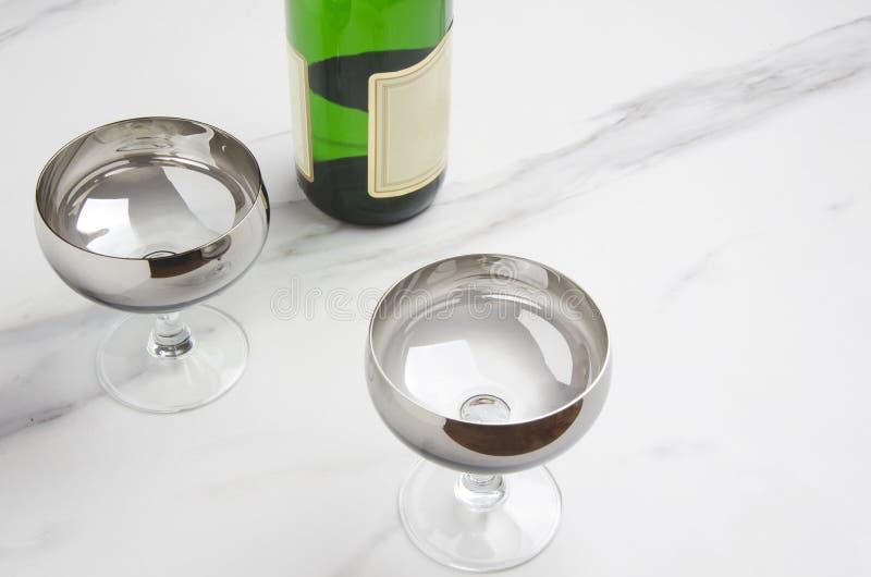 Para av exponeringsglas, den gröna flaskan av champagne på marmorerar tabellen arkivfoto
