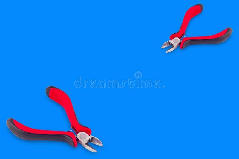 Para av pojkar för tråd med röda och svarta handtag på blå bakgrund royaltyfria bilder
