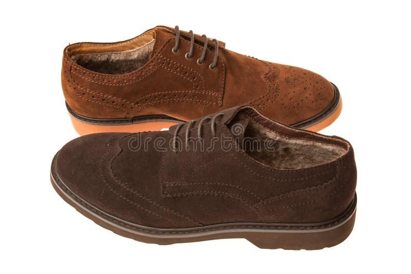 Para av skor med beståndsdelar av cowboykängor, päls och olik brun färg för skosnöre som isoleras på vit bakgrund royaltyfri bild