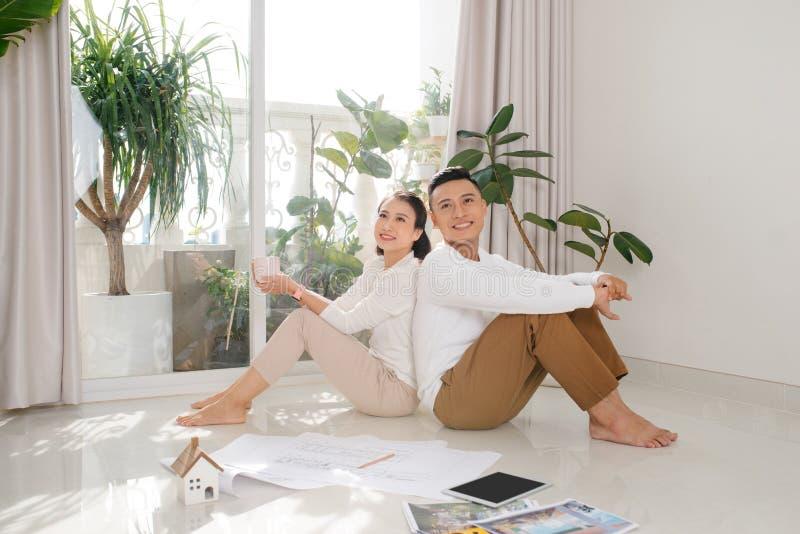 Para azjatycka siedząca na podłodze planując dekorację planu Ruchomy dom po prostu małżeństwo, różnorodność międzyrasowa obraz stock