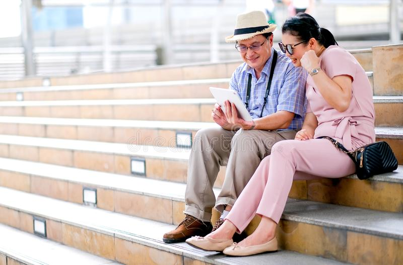 Para Azjatycki starego człowieka i kobiety turysta jest przyglądającym pastylką i działanie jak dostaje niektóre dobre wieści Ten zdjęcia stock