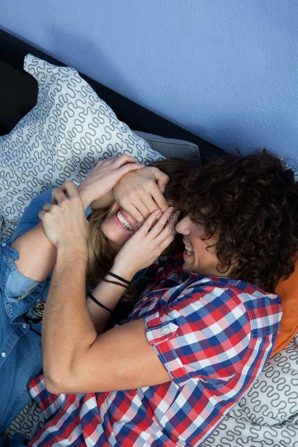 Para bawić się i śmia się na łóżku zdjęcia stock
