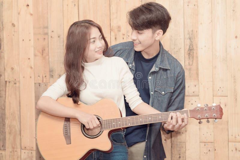 Para bawić się gitarę akustyczną zdjęcie royalty free