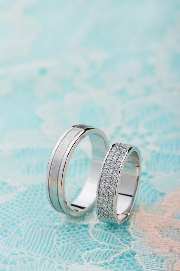 Para białego złota obrączki ślubne z diamentami na błękit koronki tle obrazy royalty free