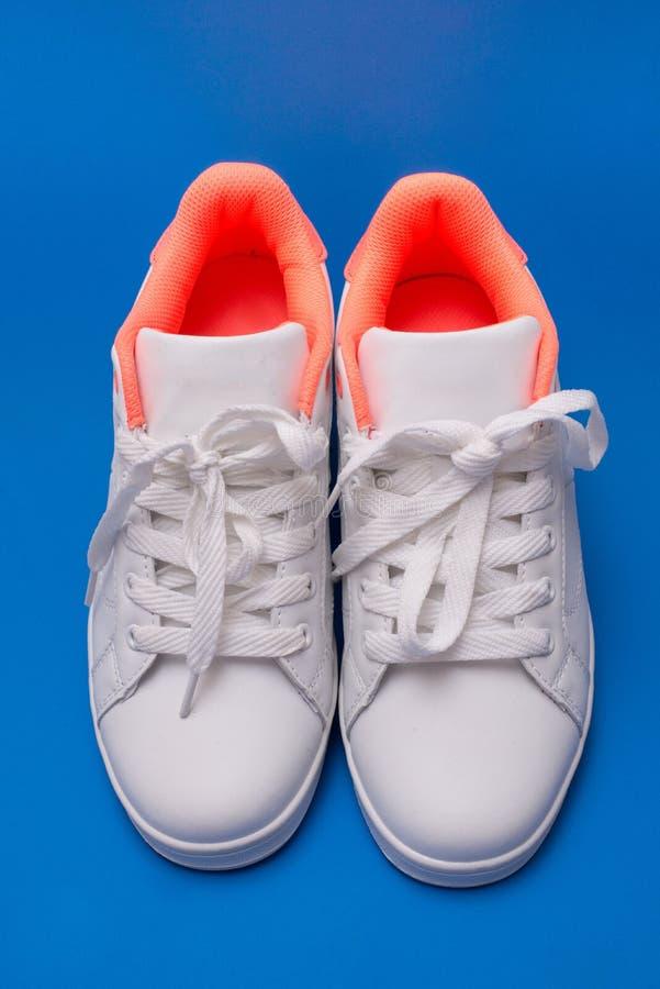 Para biali sneakers odizolowywający na błękitnym tle buta sport obraz stock