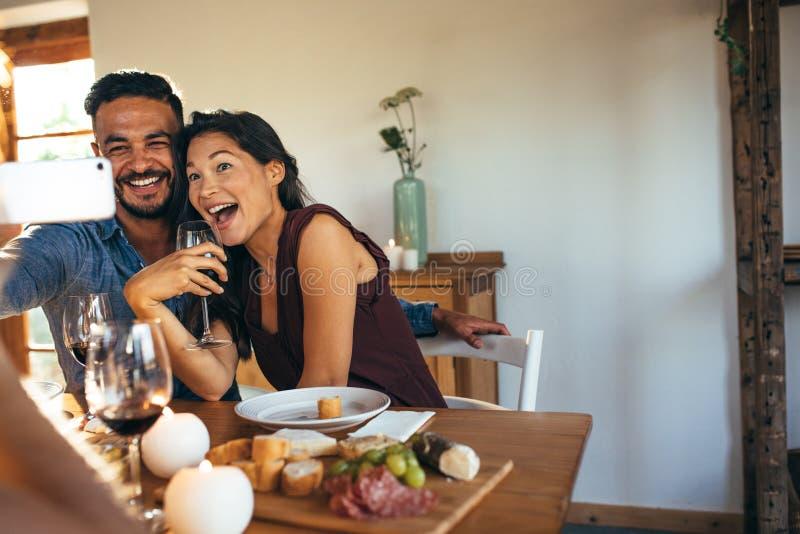 Para bierze selfie przy obiadowym przyjęciem indoors obrazy royalty free