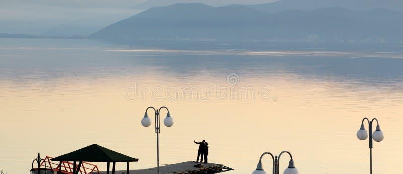 Para bierze selfy na molu na jeziornym prespa w Macedonia zachód słońca nad jezioro zdjęcia royalty free