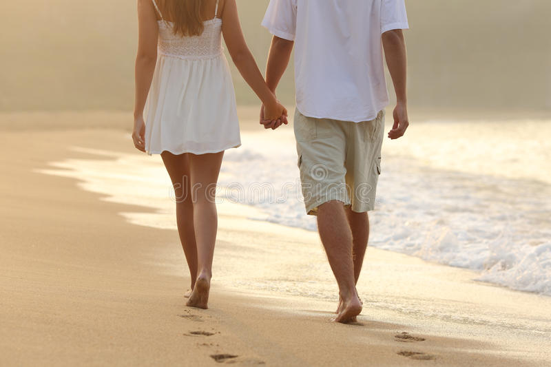 Para bierze spaceru mieniu ręki na plaży fotografia stock