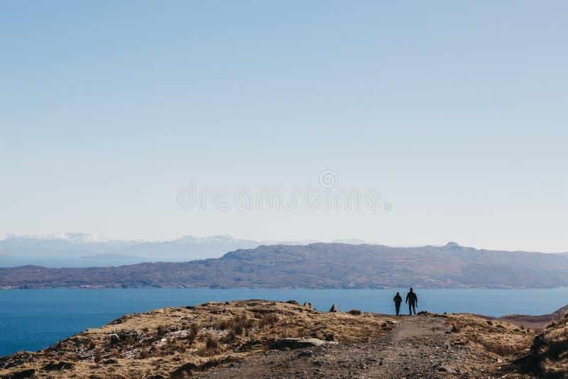 Para chodzi starego człowieka Storr spacer na wyspie Skye, Szkocja, góry i jezioro na tle, zdjęcie royalty free