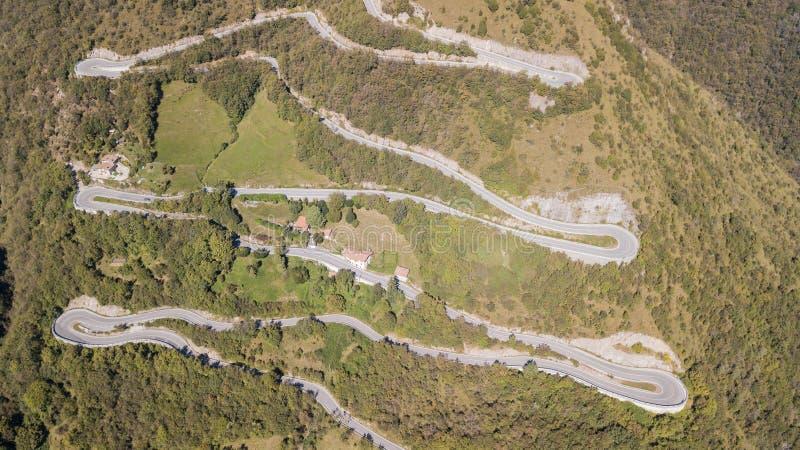 Para cima e para baixo a opinião aérea do zangão da estrada da montanha em Itália da vila de Nembro a Selvino fotos de stock