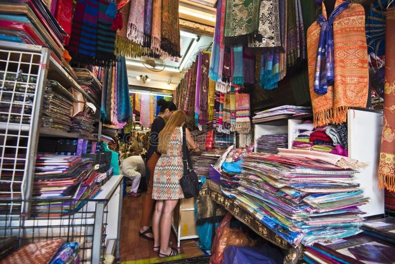 Para comprar una bufanda del pashmina o seda en el mercado de Bangkok imagen de archivo libre de regalías