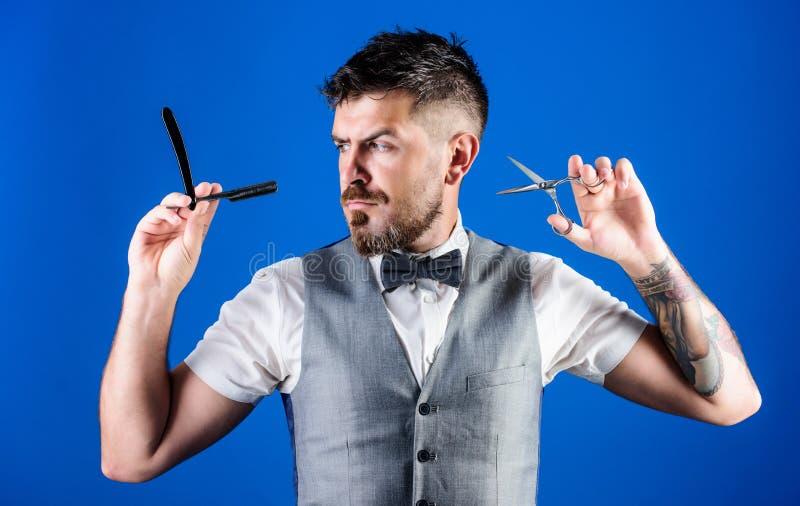 Para cortar ou barbear Homem farpado com lâmina e tesouras no barbeiro retro Barbeiro que guarda ferramentas do barbeiro do vinta fotos de stock