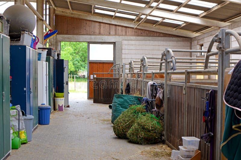 Para dentro do estábulo de equitação com tendas vazias do cavalo fotos de stock