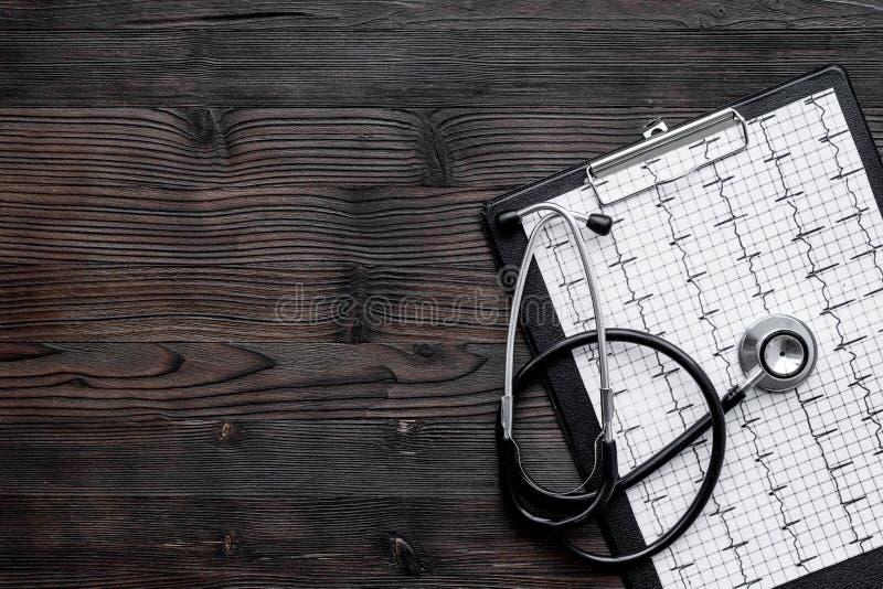 Para diagnosticar enfermedad cardíaca Cardiograma, estetoscopio en copyspace de madera oscuro de la opinión superior del fondo fotografía de archivo libre de regalías