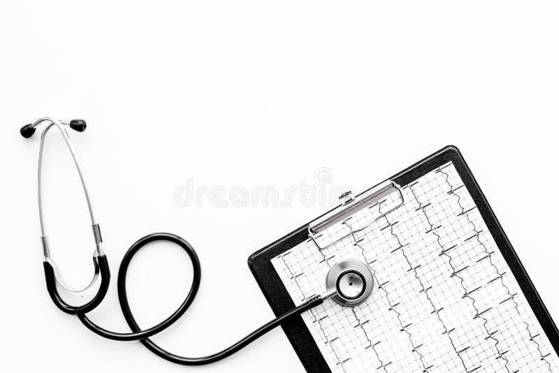 Para diagnosticar enfermedad cardíaca Cardiograma, estetoscopio en el copyspace blanco de la opinión superior del fondo foto de archivo