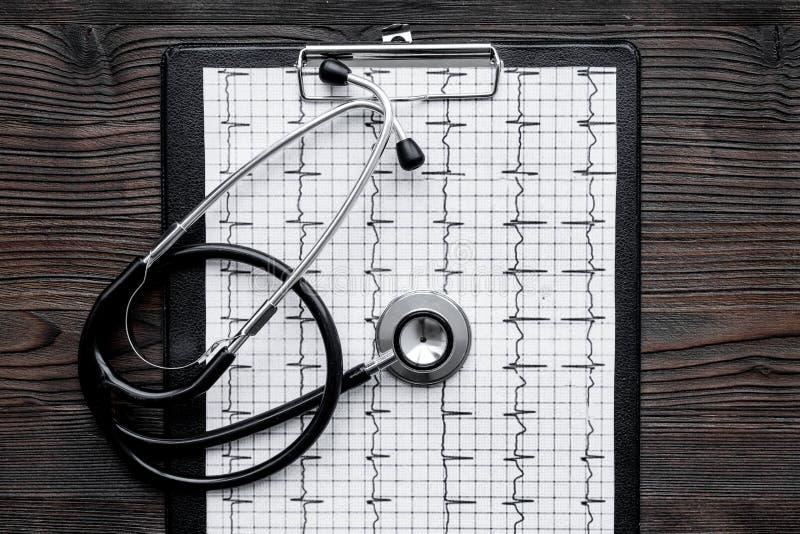 Para diagnosticar enfermedad cardíaca Cardiograma, estetoscopio en la opinión superior del fondo blanco imagen de archivo libre de regalías