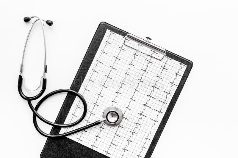 Para diagnosticar enfermedad cardíaca Cardiograma, estetoscopio en la opinión superior del fondo blanco foto de archivo libre de regalías
