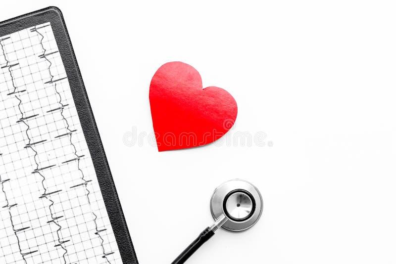 Para diagnosticar enfermedad cardíaca Muestra del corazón, cardiograma, estetoscopio en el copyspace blanco de la opinión superio imágenes de archivo libres de regalías