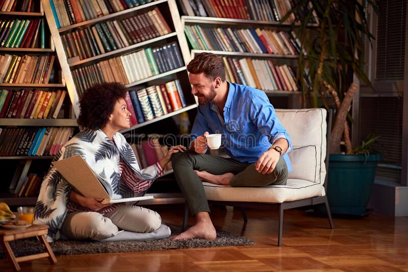 Para dobrze się bawiła w pokoju z książką i kawą obraz royalty free