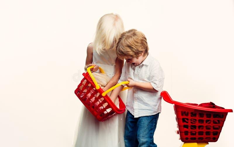 Para dzieciak?w chwyta zakupy kosza plastikowa zabawka Zakup z rabatem rodzina t?a wyst?powa? samodzielnie w white na zakupy zaku zdjęcie stock